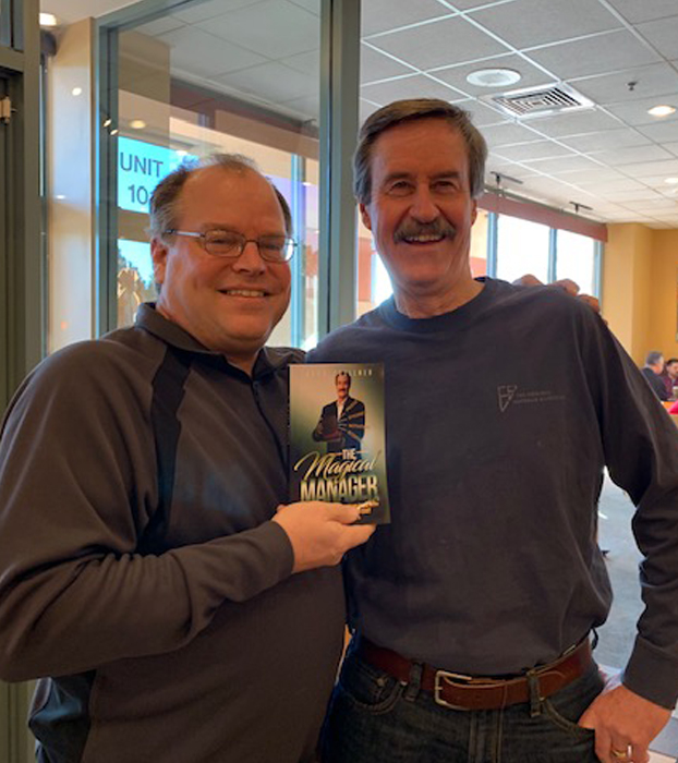 Jack Zoellner giving copy of printed book The Magical Manager to Marty Dickinson