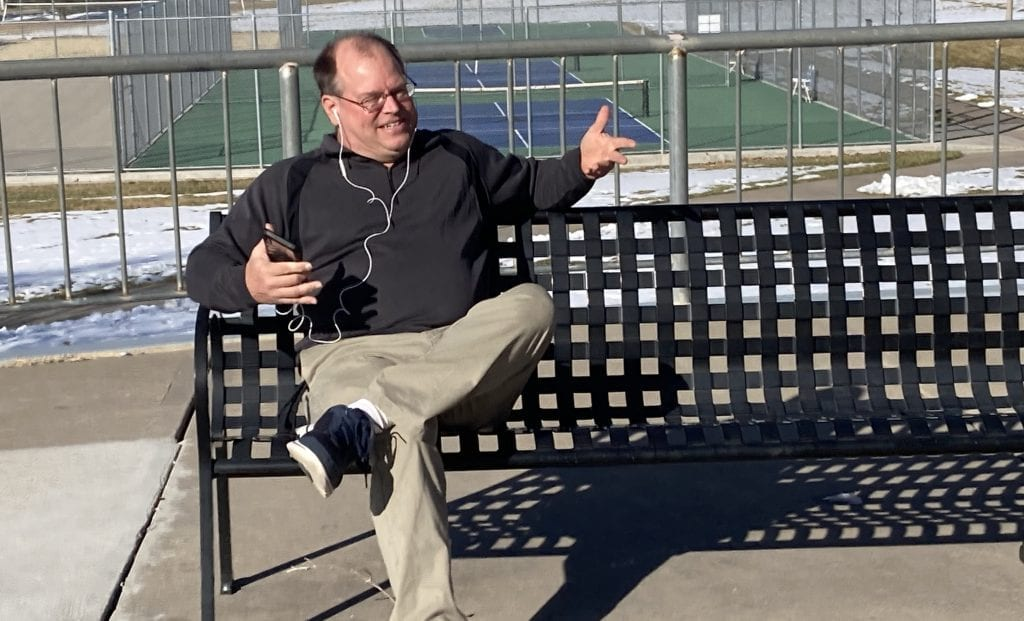 Produce My Book founder, Marty Dickinson, sitting on a park bench writing his Lions Always Win book without typing a word of the manuscript.